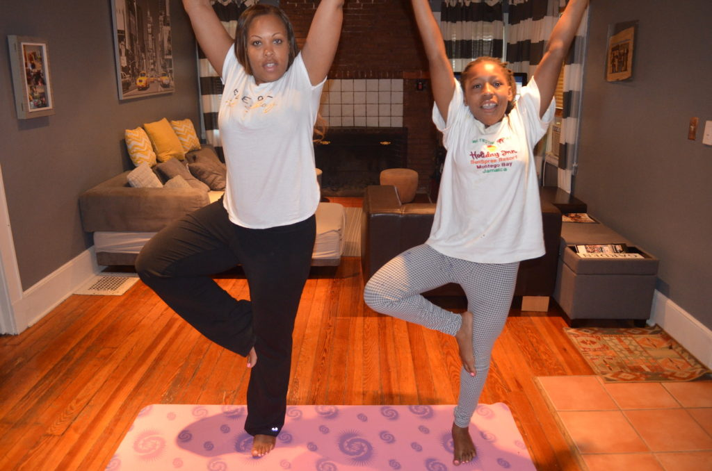 Mother and daughter practice two trees yoga position