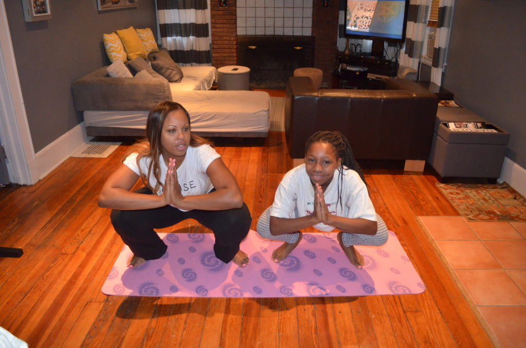 Mother and daughter practice jumping frog yoga position