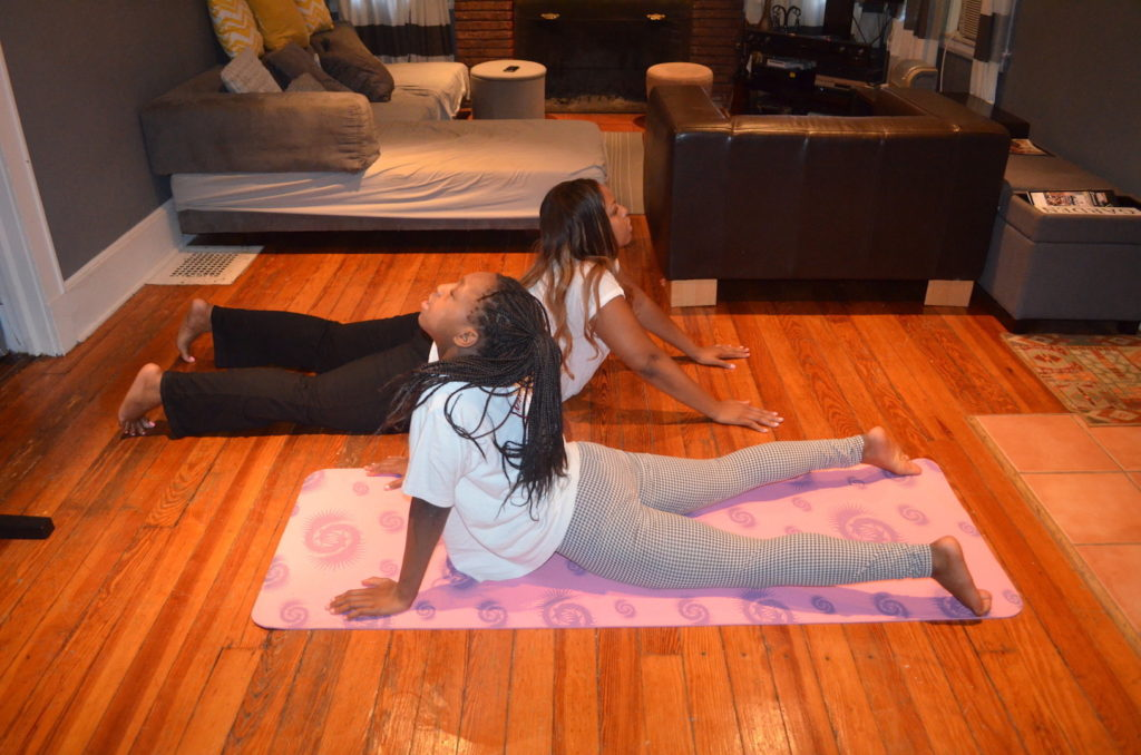 Mother and daughter practice cobra yoga position